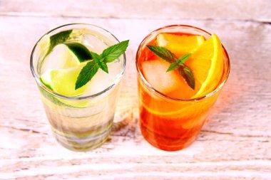 Orange and elderflower cocktails on white wooden background