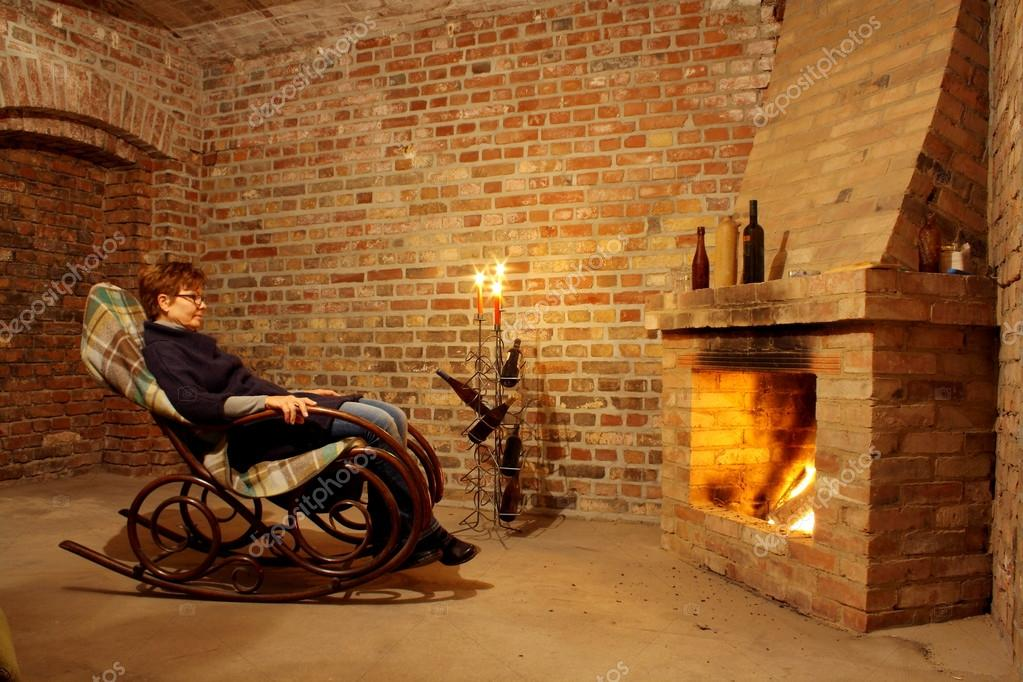 Woman In Rocking Chair By The Fireplace With Candles U2014 Stock Photo