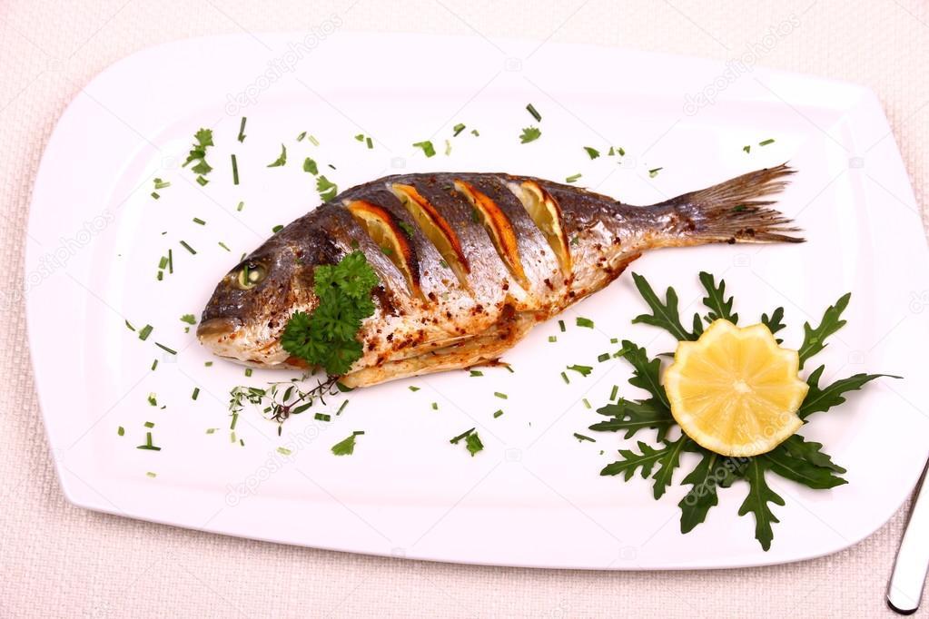 Orata grigliata di pesce limone rucola sul piatto bianco for Sea salt fish grill