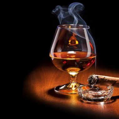 Cognac and Cigar with Smoke on dark background