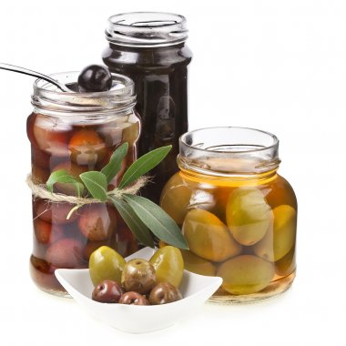 Assorted marinated olives with spices in glass jar on a white background