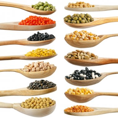 Collection of beans, legumes, peas, lentils on wooden spoons isolated on white