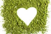 pulverisierter grüner Tee bilden Herzform isoliert auf weißem Hintergrund