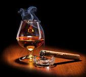 Koňak a doutníkový kouř na tmavém pozadí