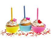 Narozeniny koláčky s sladké barevné sypání a svíčku na bílém pozadí