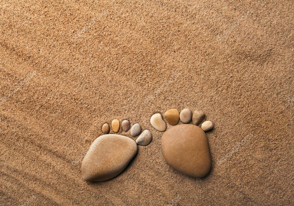 Two trace feet made of a pebble stone on the sea sand desert