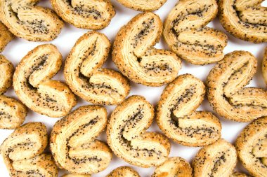 Palmiers, puff pastry cookie with poppy seeds isolated on white background