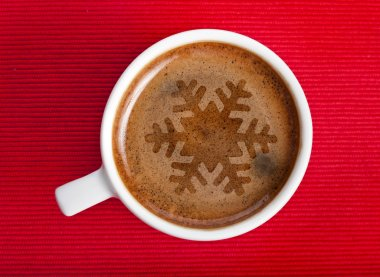 Coffee cup with christmas snow flake on red napkin background