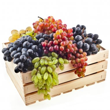 Colorful mixed grapes in a wooden crate box isolated on a white background