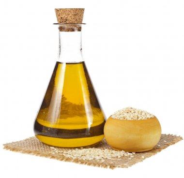 Sesame seeds and glass oil isolated on white background