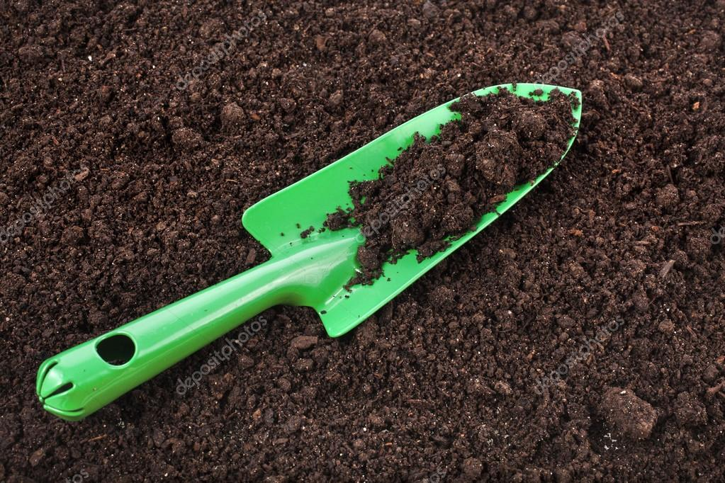 Close up of organic soil surface background and green gardening tool