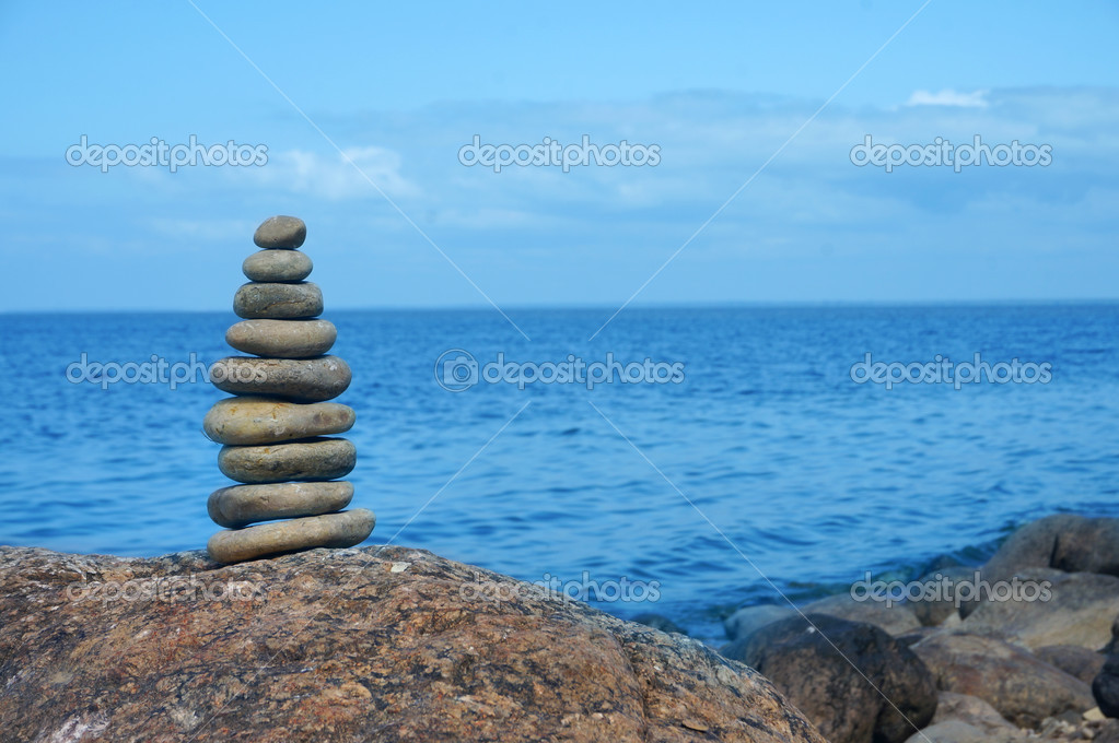 The pyramid of stone pebbles on background of the sea surface with copy space