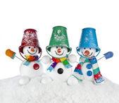 tři veselá snowmans v pruhované šály, rukavice a barevné bloku klobouk na hlavě izolovaných na bílém pozadí