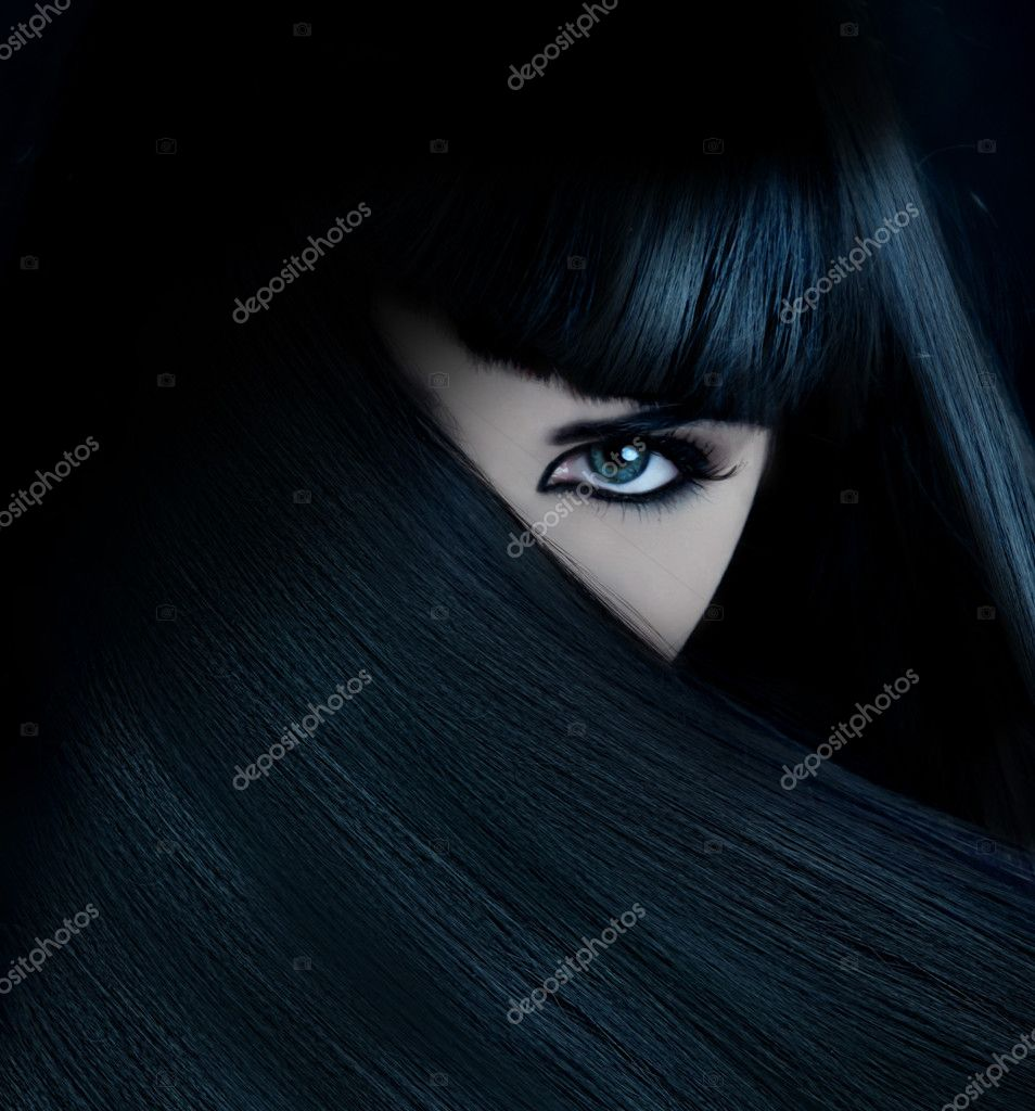 Mysterious brunette wth hair covered face and aquamarine eyes