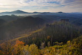 Morning mist in rocky landscape with hills and forests at fall
