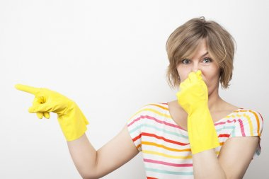 Young beautiful woman in rubber gloves holding her nose