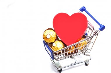 Valentine's day composition. Shopping cart full of chocolate candy and big red heart isolated on white