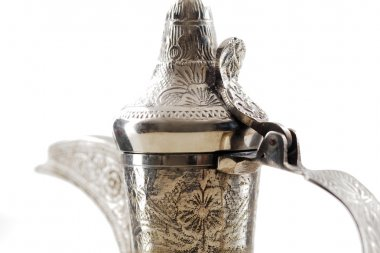 A close up of an ornate dallah, the metal pot for making Arabic coffee