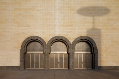 A shadow from the iconic lamps is cast over arched doors