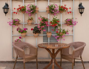 Wicker chairs and a table on the terrace with flowers