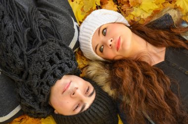 Close up image of young couple relaxing on autumn leaves
