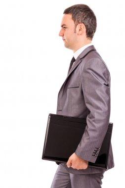 Portrait of a young businessman holding a laptop under his arm