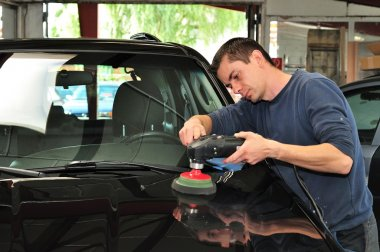 Worker polishing a car bonnet.