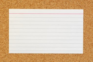 lined index card on cork board background