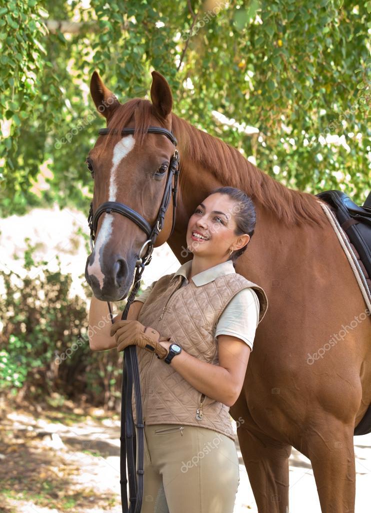 porträt einer schönen reiterin die mit pferd im freien