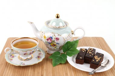 Teapot and cup of tea with brownies