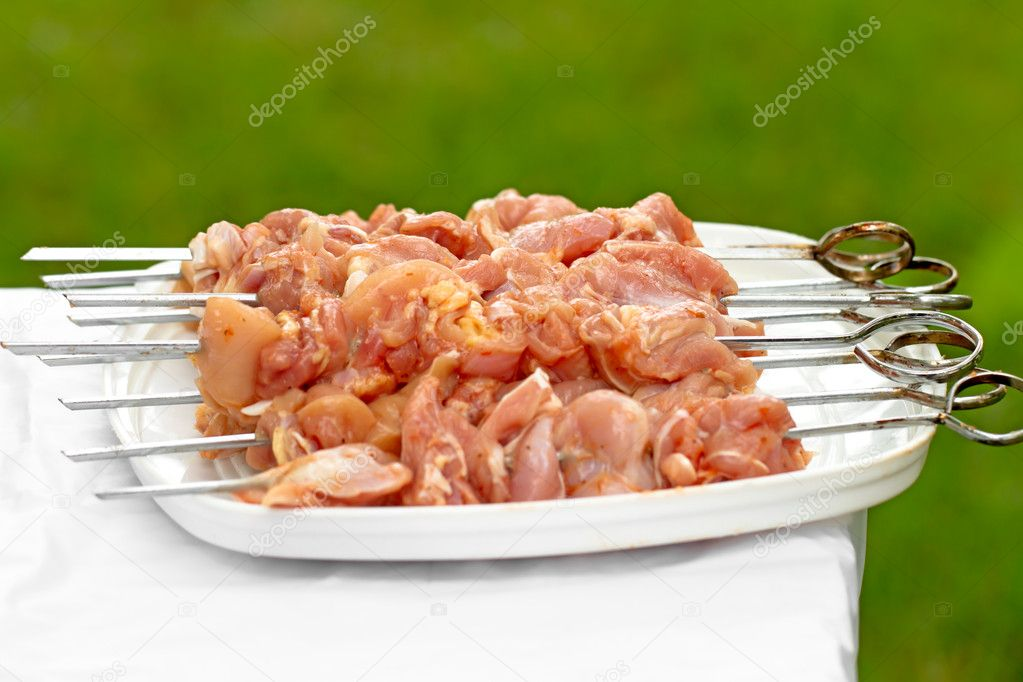Raw chicken skewers on BBQ