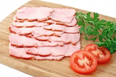 Smoked slices of ham on wooden cutting board