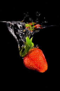 Strawberry drop into water