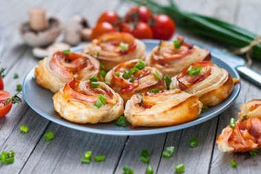 Puff pastry rolls with ham and chese. Baked snacks