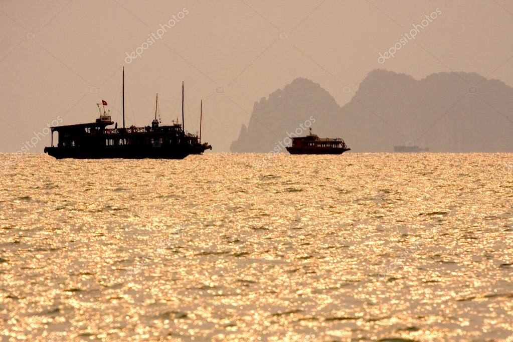 Traditional Vietnamese wooden boats sail in Halong Bay at sunset, Vietnam, South East Asia.