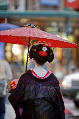 Geisha with red umbrella in Kyoto, Japan