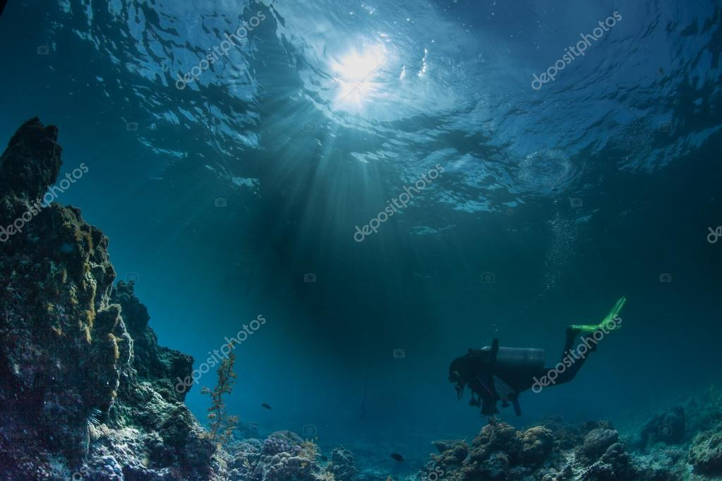 Diver swimming deeply under water