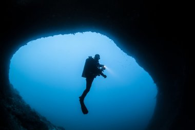 Cave divers in silhouette