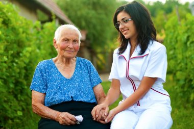 Caring doctor with sick elderly woman outdoors
