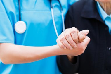 Caring Nurse holding Elderly Hands