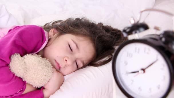 kis lány felébred, ébresztőóra közelről