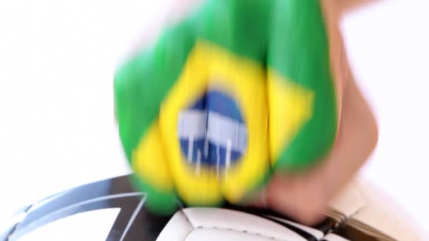 Male fist with brazilian flag on it hits football soccer ball