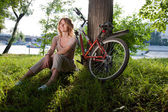 Girl sits with a bicycle