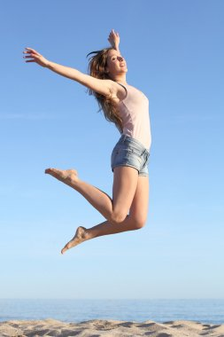 Beautiful woman jumping happy on the beach