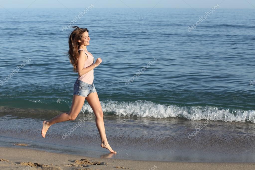 Beautiful casual woman running on the beach