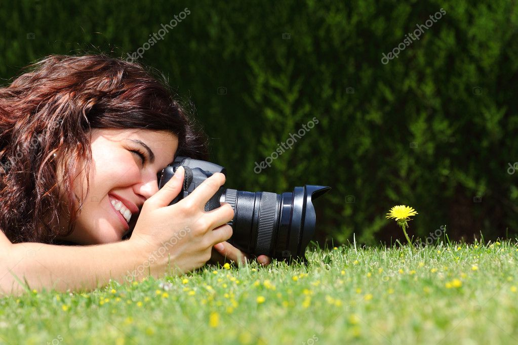 Beautiful woman taking a photography of a flower on the grass