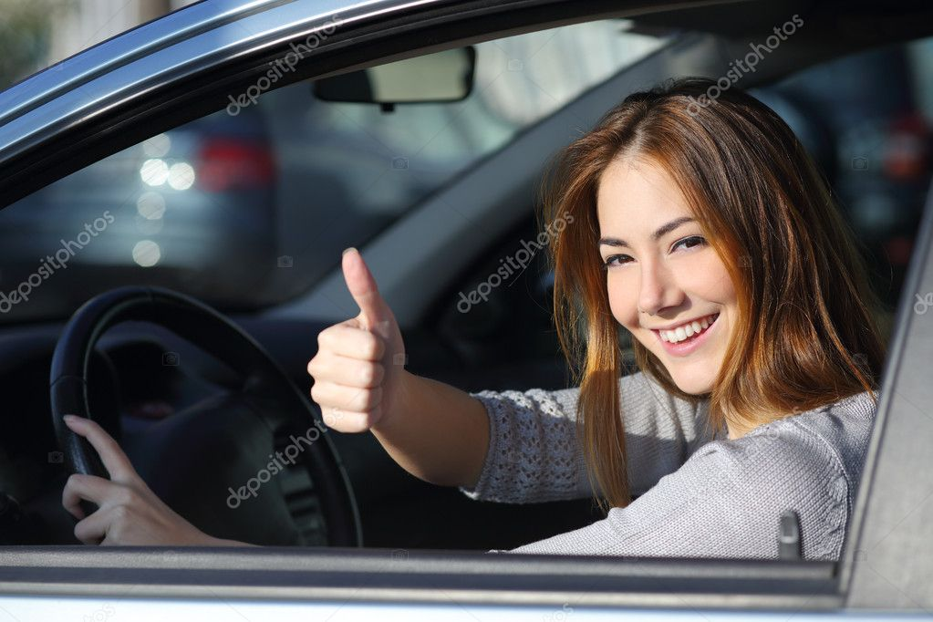 Happy woman inside a car gesturing thumb up