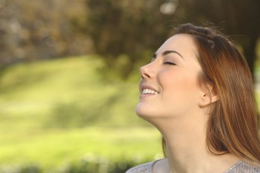 Beautiful woman doing breathing deep exercises in a park