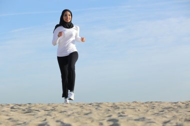 Front view of an arab saudi emirates woman running on the beach