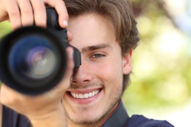 Front view of a photographer photographing with a dslr camera